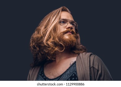Close-up portrait of a redhead hipster male with long luxuriant hair and full beard dressed in casual clothes standing in a studio, looking away. Isolated on the dark background.