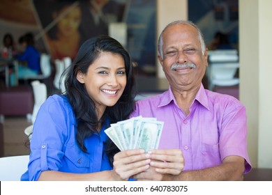 Closeup portrait rich elderly gentleman in pink shirt and lady in blue top holding greenbacks. Booming economy concept, buy, sell, award. Make money at home
