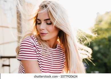 Close-up portrait of romantic girl with long blonde hair relaxing on balcony in sunny day. Charming young woman with nude make-up posing with eyes closed during outdoor photoshoot.
