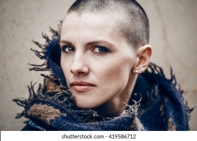 Closeup portrait of sad beautiful Caucasian white young bald girl woman with shaved hair head in leather jacket and scarf shawl, spiritual mood state of mind, conceptual art, peaceful warrior