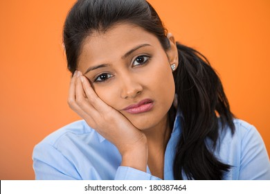 Closeup portrait of sad, depressed, stressed, thoughtful young woman, full of worries, looking at you, isolated on orange background. Human face expressions, emotions, feelings, reaction, attitude