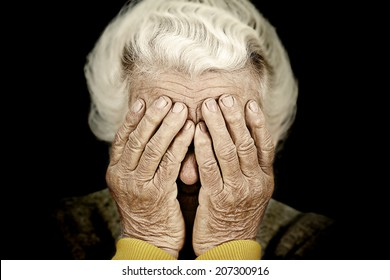Closeup portrait sad depressed, stressed, thoughtful, senior, old woman, gloomy, worried, covering her face, isolated black background. Human face expressions, emotion, feelings, reaction, attitude