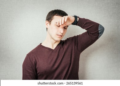 Closeup portrait sad depressed stressed, alone disappointed gloomy young man having headache, regrets, many thoughts isolated orange background. Human emotion facial expression feeling body language