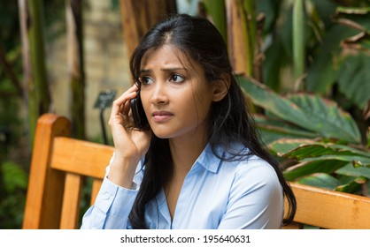 Closeup portrait, sad, depressed, unhappy worried young woman talking on phone, sitting on bench, isolated trees background. Negative human emotions, facial expressions, feelings, reaction. Bad news.