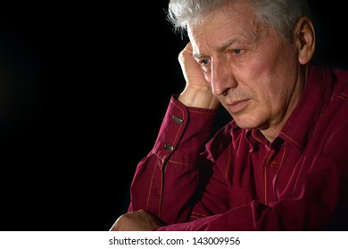 close-up portrait of a sad elderly man on a black background