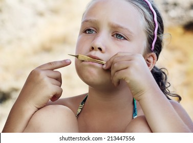 Close-up portrait of sad little girl which playing on vargan on outdoors