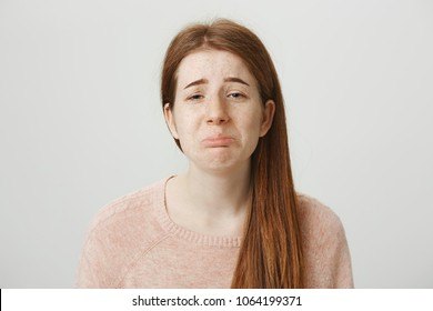 Close-up portrait of sad redhead caucasian girl with gloomy smile, whining or crying with frowned eyebrows and miserable look, standing over gray background. Woman upset because she do not have couple