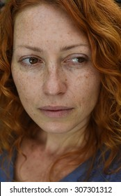 closeup portrait of sad redhead woman without makeup looking back