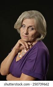Close-up portrait of sad senior woman isolated on black background