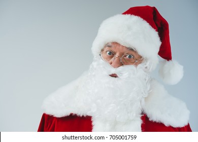 close-up portrait of santa claus in hat and eyeglasses looking at camera isolated on white