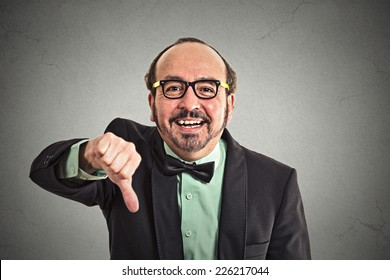Closeup portrait sarcastic middle aged man showing thumbs down sign hand gesture happy someone made mistake lost failed isolated grey wall background. Negative emotion face expression feeling attitude