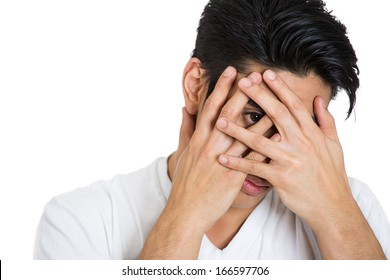 Closeup portrait of scared shy man covering face nose and mouth with hands fingers, peering through with one wide eye isolated on white background. Negative emotion facial expression feeling
