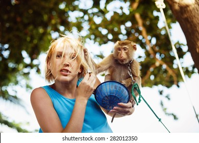 A closeup portrait of a scared woman attacked by a domestic macaque. Monkey is grabbing woman by hair. Concept of monkey aggression.