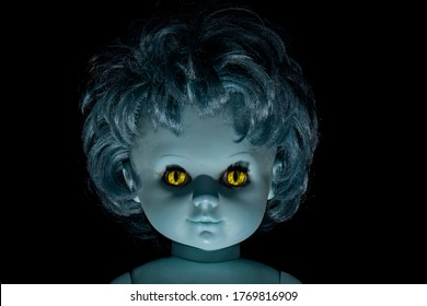 Close-up portrait scary vintage doll face with pale blue zombie skin and yellow terrible vampire eyes against black background. Halloween concept