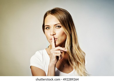Closeup portrait secretive young woman placing finger on lips asking shh, quiet, silence looking sideway isolated gray background.