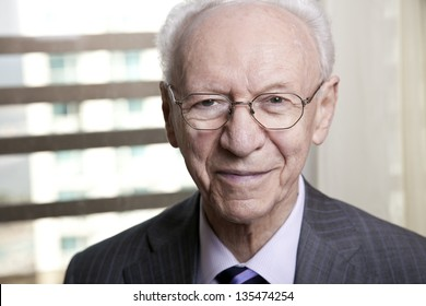 Close-up portrait of a senior businessman (in his 80's) smiling to the camera wearing a suit and tie, as well as old fashion glasses.