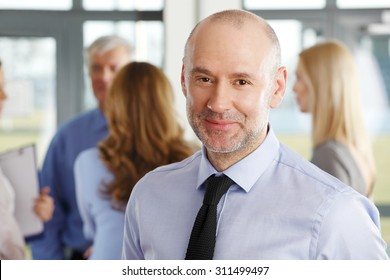 Close-up portrait of senior businessman standing at business meeting while looking at camera and smiling. Business people standing in background.