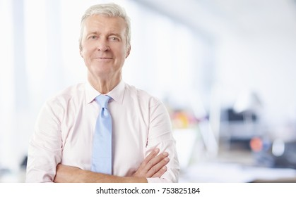 Close-up portrait of a senior businessman standing with arms crossed at the office while looking at camera and smiling.
