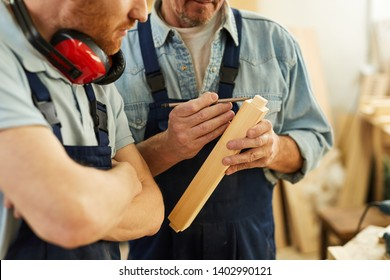 Closeup portrait of senior carpenter teaching apprentice  while working  in joinery workshop, copy space