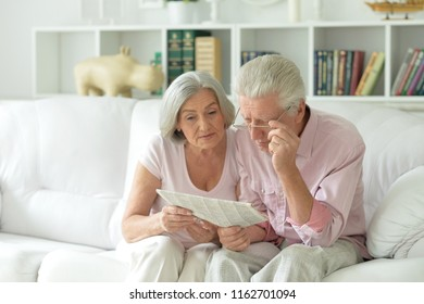 Close-up portrait of a  senior couple with newspaper
