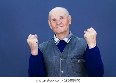Closeup portrait senior elderly happy man, grandfather posing showing his strong body, spirit, fists up in air isolated blue background. Human emotion facial expression, body language, life perception