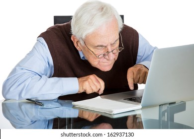 Closeup portrait of senior elderly mature man with glasses having eyesight problems trying to type on laptop, isolated on white background. Human emotions and facial expressions. Age related changes.