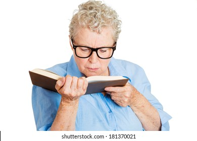 Closeup portrait of senior female, mature woman, old lady with trouble, problems reading book having bad vision, isolated white background. Emotions, facial expressions. Geriatric aging health issues