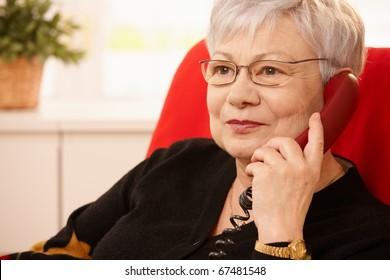 Closeup portrait of senior lady on landline phone call, smiling.
