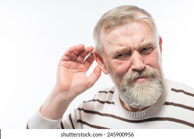 Closeup portrait, senior man, grandfather hard of hearing, placing hand on ear asking someone to speak up, isolated white background. Negative emotion, facial expressions, feelings, reaction, aging