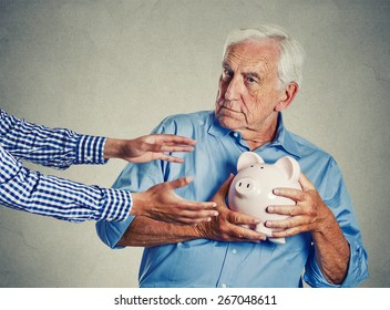 Closeup portrait senior man grandfather holding piggy bank looking suspicious trying to protect his savings from being stolen isolated on gray wall background. Financial fraud concept