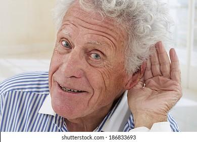 Closeup portrait, senior man, hard of hearing, placing hand on ear asking someone to speak up