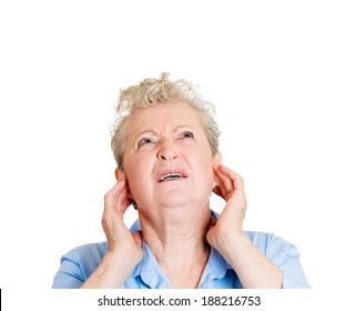 Closeup portrait, senior mature angry, unhappy, stressed, woman covering her ears, looking up, to say, stop making that loud noise giving me a headache, isolated white background. Negative emotion