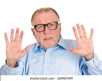 Closeup portrait, senior mature business man in glasses telling you to slow down, no stop right there, with hands in air, isolated white background. Negative human emotion, facial expression, feelings