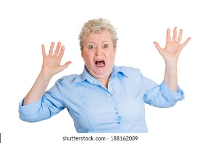 Closeup portrait, senior mature business woman looking shocked, surprised in full disbelief, hands in air, isolated white background. Negative human emotions, facial expressions, feelings, reaction