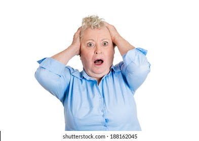 Closeup portrait, senior mature business woman looking shocked, surprised in full disbelief, hands on head, isolated white background. Negative human emotions, facial expressions, feelings, reaction
