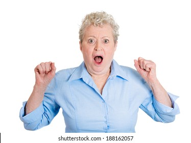 Closeup portrait, senior mature business woman looking shocked, surprised in full disbelief, fists in air, isolated white background. Negative human emotions, facial expressions, feelings, reaction