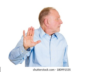 Closeup portrait of senior mature grumpy man with bad attitude giving talk to hand gesture with palm outward, isolated on white background. Negative emotions, facial expression feelings, body language