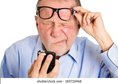 Closeup portrait, senior mature man, nerd black glasses, having trouble seeing cell phone screen because of vision problems. Bad text message. Negative human emotion facial expression feelings.