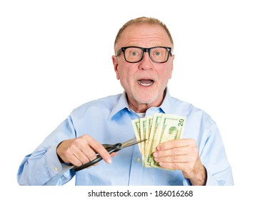 Closeup portrait, senior mature man, business worker employee, corporate agent representative cutting budget, trimming dollar bills, cash, money with scissors, isolated white background. Emotions