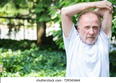 Closeup portrait, senior mature man in white shirt, stretching arms, isolated green trees background. Warming up