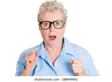 Closeup portrait, senior mature, nerd business woman in black glasses looking shocked, fists in air, isolated white background. Negative human emotions, facial expressions, feelings, reaction