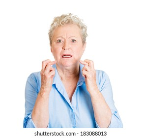 Closeup portrait senior mature woman crossing her fingers, hoping for best future, looking at you, in anticipation for life changer, isolated white background. Human emotions, facial expressions