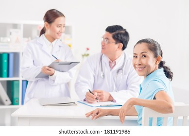 Close-up portrait of a senior patient looking at camera while doctor and nurse discussing on the foreground