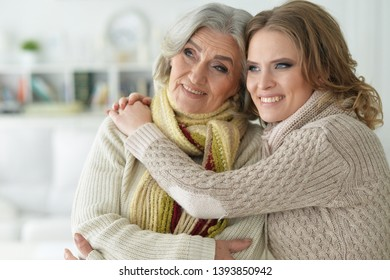Close-up portrait of senior woman with daughter covering with blanket