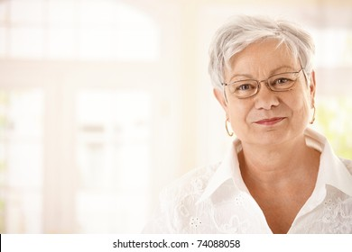 Closeup portrait of senior woman with glasses, looking at camera, smiling.
