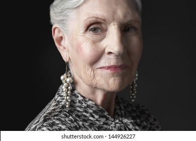 Closeup portrait of a senior woman with pearl earrings against black background