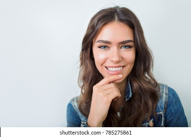 Close-up portrait of sensitive woman with dark hair and big green eyes smiles over grey wall with fantastic smile.