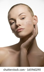 close-up portrait of sensual blonde woman applying white cosmetics on her clear skin. Beauty treatment concept