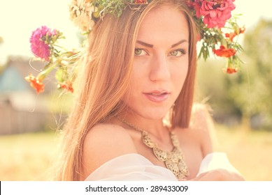 closeup portrait of sensual blonde young pretty lady wearing flower crown having fun relaxing enjoying summer & looking at camera on green outdoors copy space background