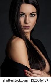 Closeup portrait of a sensual brunette lady posing black background